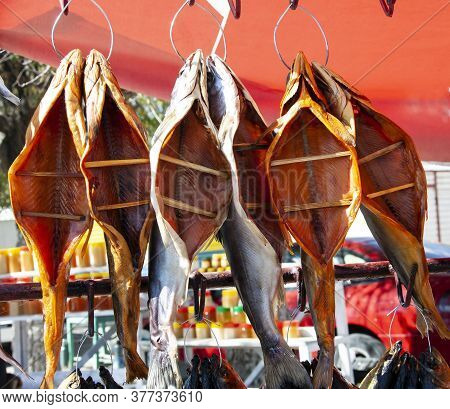 Dried Fish Hangs Over The Market Counter. Dried Salt Fish Is Prepared For Sale At The Counter Of A V