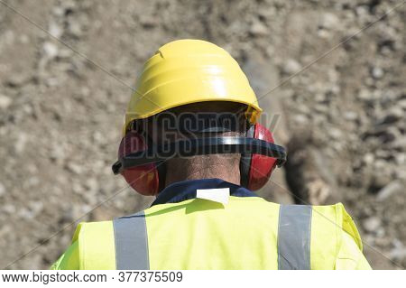 Worker At The Construction Site Wearing Helmet And Hearing Protection