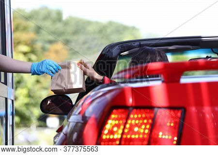 Woman In Car Picks Up Bag Of Food Closeup. Fast Food In Mcdraw Concept