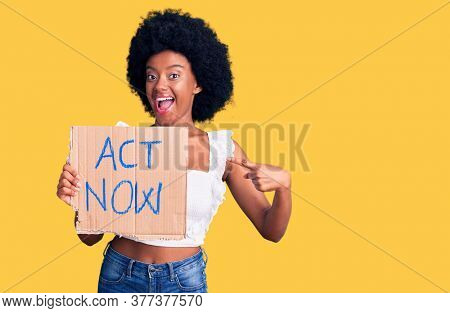 Young african american woman holding act now banner smiling happy pointing with hand and finger
