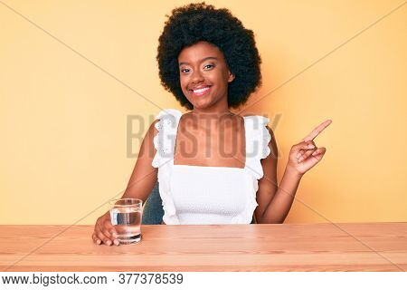 Young african american woman drinking glass of water smiling happy pointing with hand and finger to the side