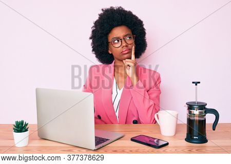 Young african american woman working at desk using computer laptop serious face thinking about question with hand on chin, thoughtful about confusing idea