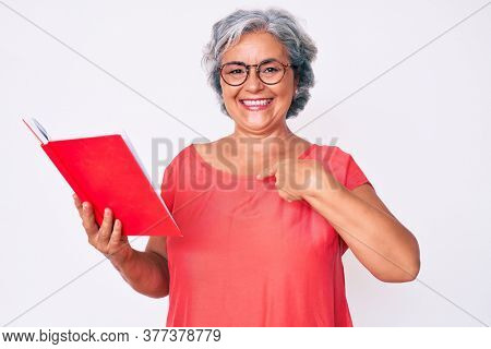 Senior hispanic woman wearing glasses holding book pointing finger to one self smiling happy and proud