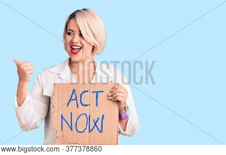 Young blonde plus size woman holding act now cardboard banner pointing thumb up to the side smiling happy with open mouth