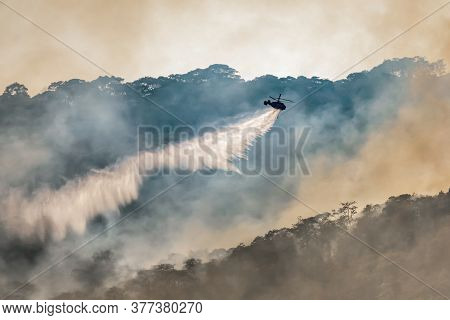 Firefighting Helicopter Dropping Water On Forest Fire