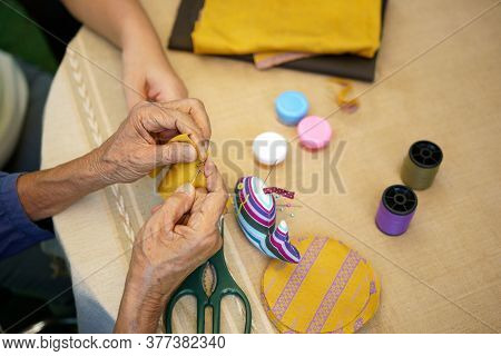 Elderly Woman With Caregiver In The Needle Crafts Occupational Therapy  For Alzheimer\'s Or Dementia