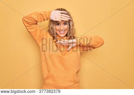 Young beautiful blonde sporty woman wearing casual sweatshirt over yellow background Smiling cheerful playing peek a boo with hands showing face. Surprised and exited
