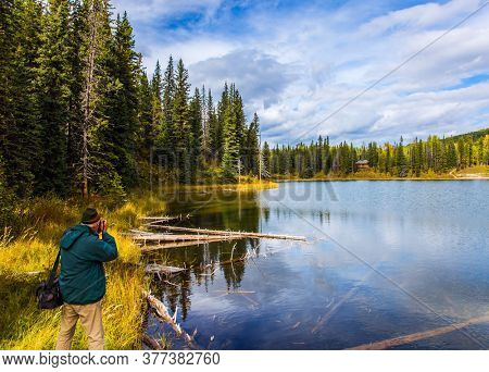 Middle-aged man in a jacket photographs a lake. Northern Cordillera. Cold cloudy autumn day. The Northern Rocky Mountains. The concept of ecological, active and photo tourism