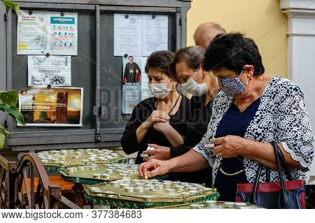 Uzhgorod, Ukraine - July 20, 2020: Women In Protective Masks Light Candles During The Farewell Cerem