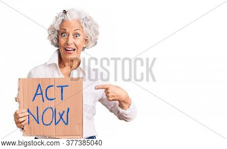 Senior grey-haired woman holding act now banner smiling happy pointing with hand and finger