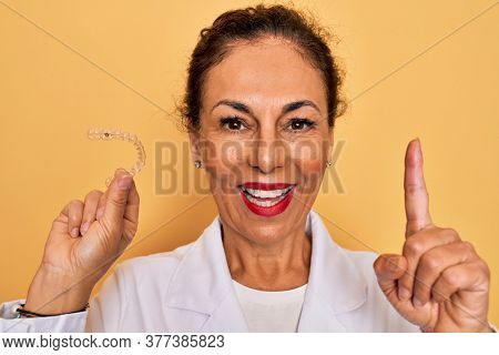 Middle age senior dentist woman holding clear aligner for teeth correction surprised with an idea or question pointing finger with happy face, number one