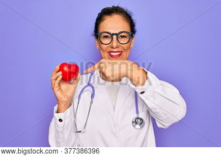 Middle age senior cardiologist doctor woman holding red heart over purple background very happy pointing with hand and finger