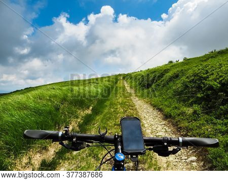 Cycling Through The Mountains Using A Navigator. Summer Outdoor Recreation. Cycling Tourism. Sunny W
