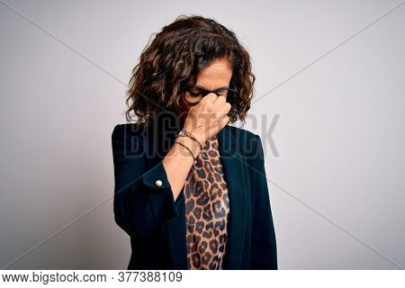 Middle age brunette business woman wearing glasses standing over isolated white background tired rubbing nose and eyes feeling fatigue and headache. Stress and frustration concept.