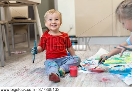 Adorable Cute Caucasian Little Blond Siblings Children Enjoy Having Fun Painting With Brush And Palm