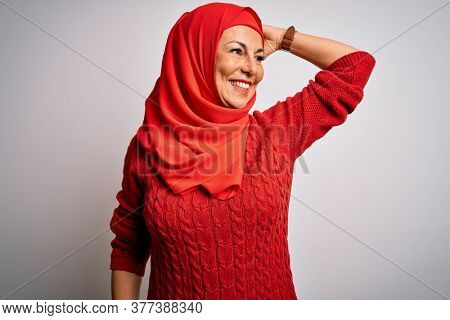 Middle age brunette woman wearing muslim traditional hijab over isolated white background smiling confident touching hair with hand up gesture, posing attractive and fashionable