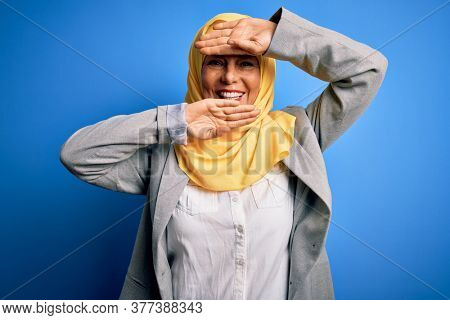 Middle age brunette business woman wearing muslim traditional hijab over blue background Smiling cheerful playing peek a boo with hands showing face. Surprised and exited
