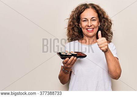 Middle age beautiful woman holding tray with maki sushi over isolated white background smiling happy and positive, thumb up doing excellent and approval sign