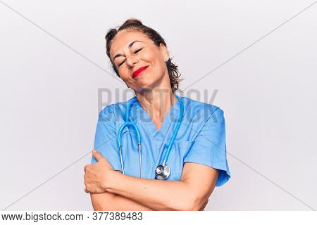 Middle age brunette nurse woman wearing uniform and stethoscope over white background hugging oneself happy and positive, smiling confident. Self love and self care