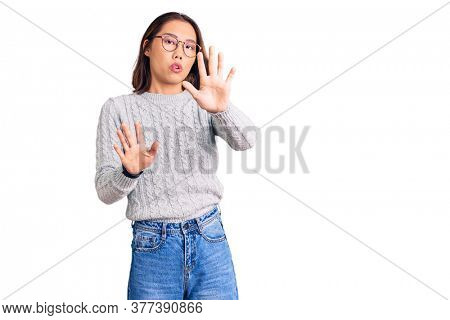Young beautiful chinese girl wearing casual clothes moving away hands palms showing refusal and denial with afraid and disgusting expression. stop and forbidden.