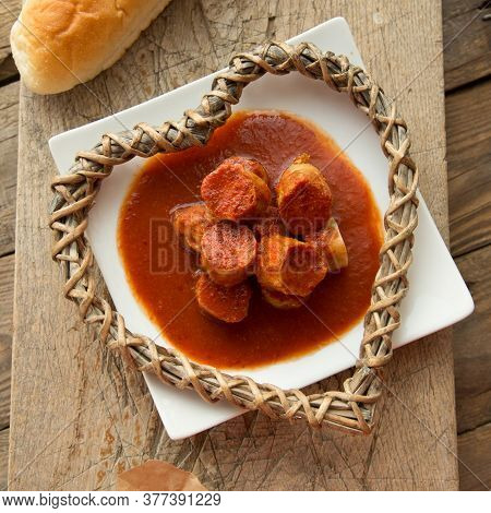Sausage With Curry Sauce On White Plate Served To Eat. Curry Lovers Food Appetizer.