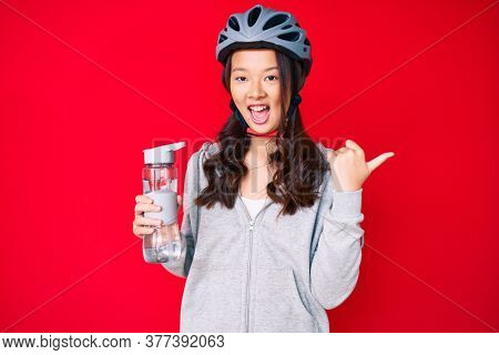 Young beautiful chinese girl wearing bike helmet and holding water bottle pointing thumb up to the side smiling happy with open mouth