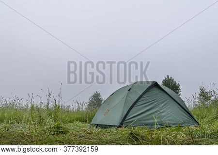 A Green Camping Tent Stands On The Grass. Morning, Heavy Fog. Tourism And Hiking