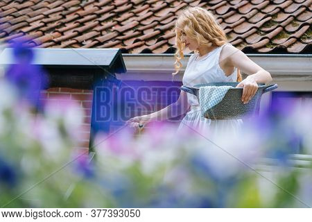 Woman In White Dress Holding Basin Near Ancient Artesian Draw-well In Village. Colorful Violet Flowe