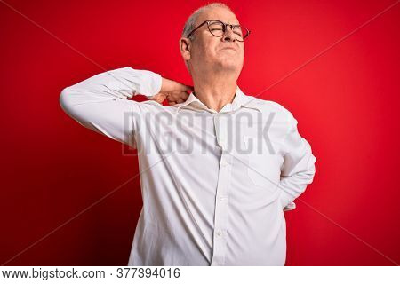 Middle age handsome hoary man wearing casual shirt and glasses over red background Suffering of neck ache injury, touching neck with hand, muscular pain