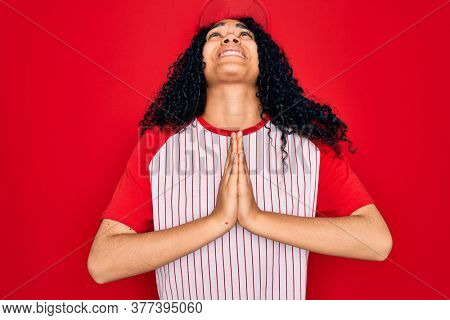 Young african american curly sportswoman wearing baseball cap and striped t-shirt begging and praying with hands together with hope expression on face very emotional and worried. Begging.