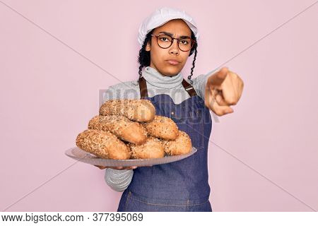 Young african american baker woman wearing apron holding wholemeal bread with cereal pointing with finger to the camera and to you, hand sign, positive and confident gesture from the front