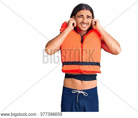 Young handsome man wearing nautical lifejacket covering ears with fingers with annoyed expression for the noise of loud music. deaf concept.