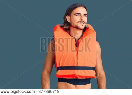 Young handsome man wearing nautical lifejacket looking away to side with smile on face, natural expression. laughing confident.
