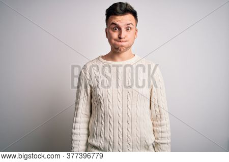 Young handsome caucasian man wearing casual winter sweater over white isolated background puffing cheeks with funny face. Mouth inflated with air, crazy expression.