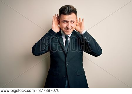 Young handsome business man wearing elegant suit and tie over isolated background Trying to hear both hands on ear gesture, curious for gossip. Hearing problem, deaf