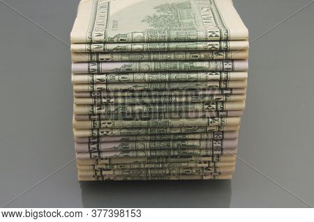 Stack Of American Money, One Hundred Dollar Cash On A Dark Background, A Lot Of One Hundred Dollar B