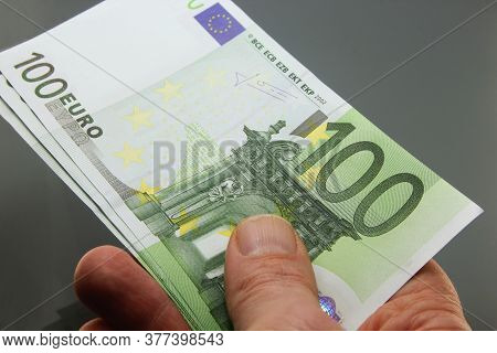 Stack Of Euros Money In Hand, Hundred Euro Banknotes In Cash On Dark Background, Many Twenty Euro Ba