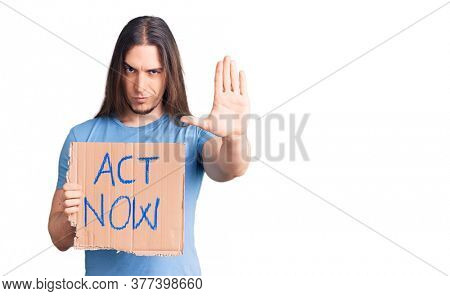 Young adult man with long hair holding act now banner with open hand doing stop sign with serious and confident expression, defense gesture