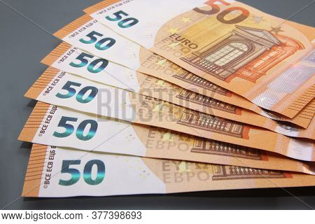 Stack Of Various Fifty Euro Bills, Fifty Euro Cash Bills On Dark Background.