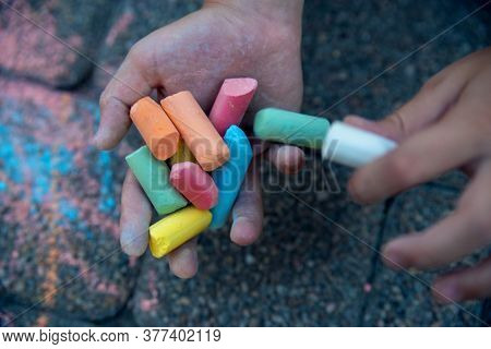 Close-up Of Colored Chalk In The Hands Of A Child. Concept Of Choice, Decision Making, Dilemma, Prob