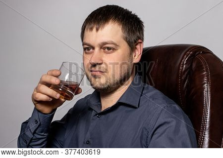 A Handsome Young Man Of 30-35 Years Old In A Shirt Sits On A Brown Leather Armchair And Holds A Glas