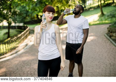 Photo Of Young Beautiful Caucasian Woman Holding Water Bottle After Training In The Park. Handsome A