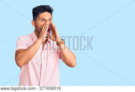 Handsome latin american young man wearing casual summer shirt shouting angry out loud with hands over mouth