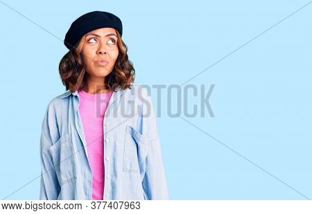 Young beautiful mixed race woman wearing french look with beret smiling looking to the side and staring away thinking.