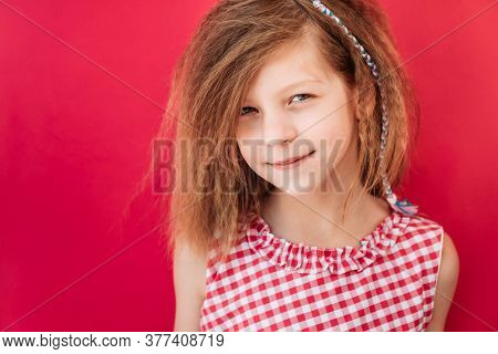 Little Blonde Girl In Red Checkered Dress Smirking, Isolated On Pink Background