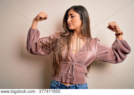 Young beautiful brunette elegant woman with long hair standing over isolated background showing arms muscles smiling proud. Fitness concept.