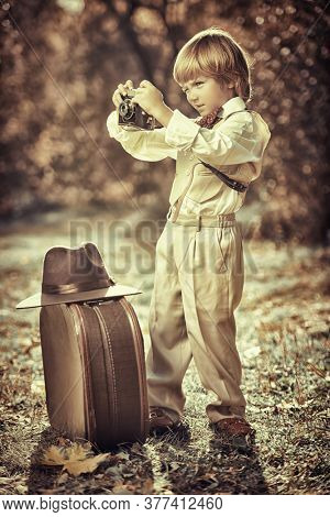 Happy little boy stands with his old fashioned camera in a beautiful autumn park. Retro style. Children's fashion.