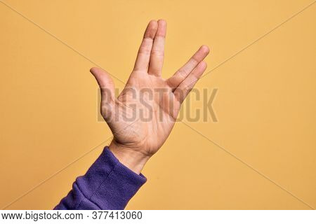 Hand of caucasian young man showing fingers over isolated yellow background greeting doing Vulcan salute, showing hand palm and fingers, freak culture