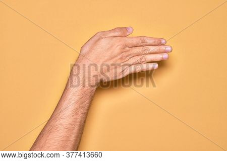 Hand of caucasian young man showing fingers over isolated yellow background stretching and reaching with open hand for handshake, showing back of the hand
