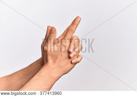 Hand of caucasian young man showing fingers over isolated white background gesturing fire gun weapon with fingers together, aiming shoot symbol